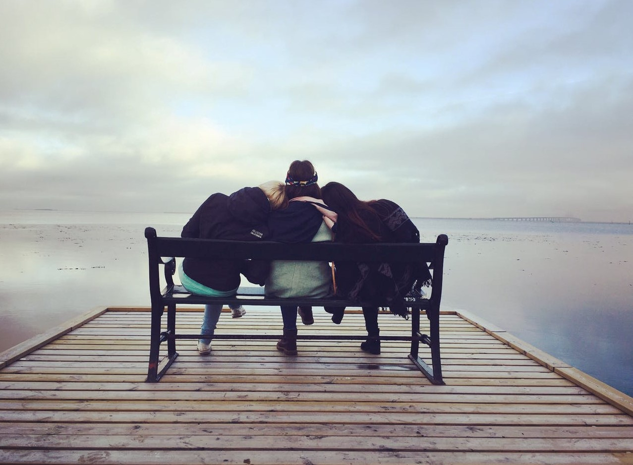 Three friends sitting on a bench on a wooden dock above water.